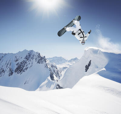 snowboarder backflipping off a backcountry jump in the sun