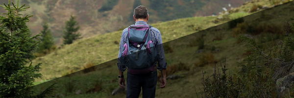man with backpack hiking over grassy hills